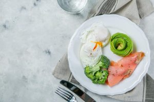 A photo of typical meal on the keto diet: poached eggs, raw broccoli, avocado slices, and smoked salmon.